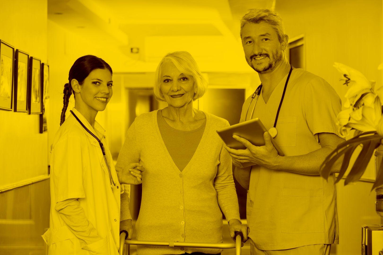 Ärztin Pfleger und Seniorin stehen während Pfleger Tablet mit Easysoft in der Hand hält