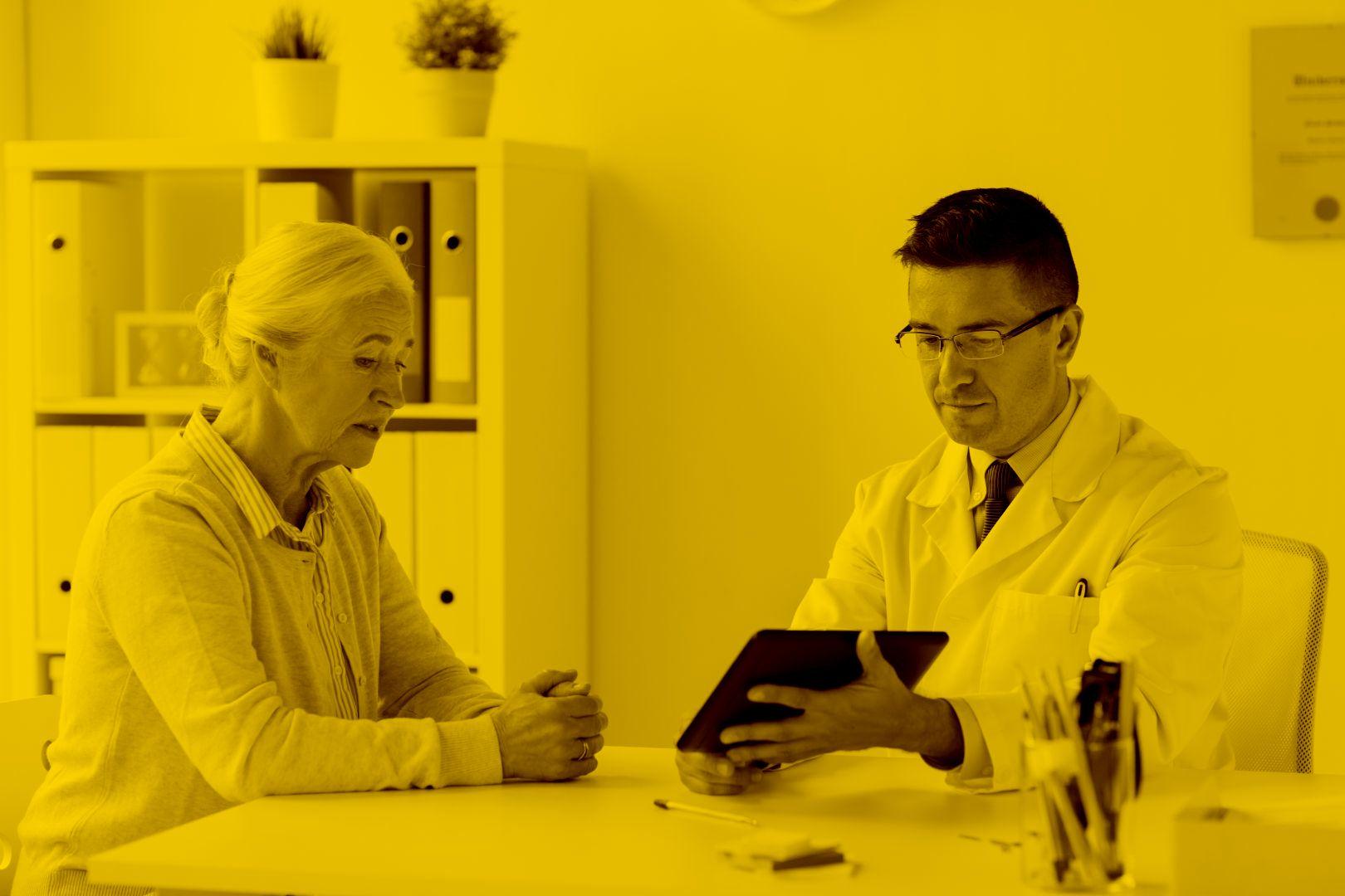 Arzt hat Besprechung mit Seniorin, hat dabei Tablet in der hand mit Acs in der maja.cloud
