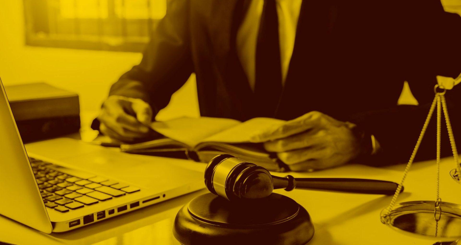 Anwalt arbeitet am Macbook mit Anwaltssoftware und liest ein Gesetzbuch