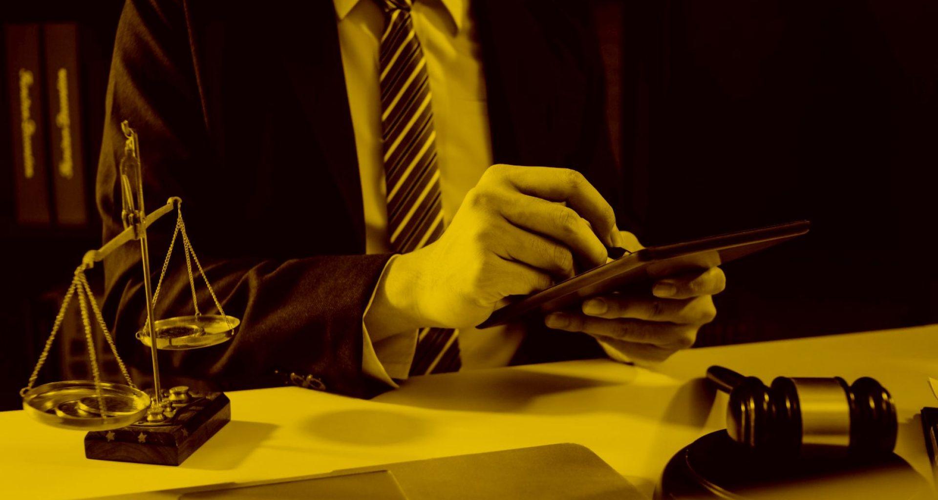 Anwalt arbeitet am Tablet mit Anwaltssoftware im Büro