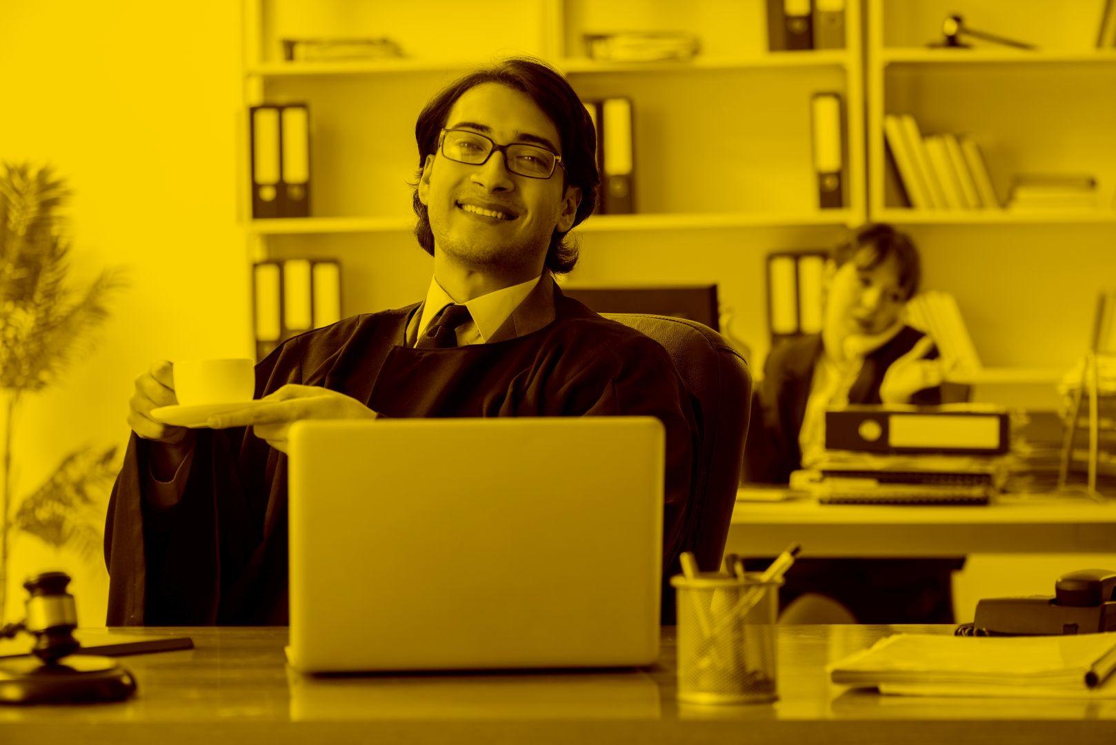 Anwalt arbeitet mit Anwaltssoftware im Büro mit einer Tasse Kaffee in der Hand
