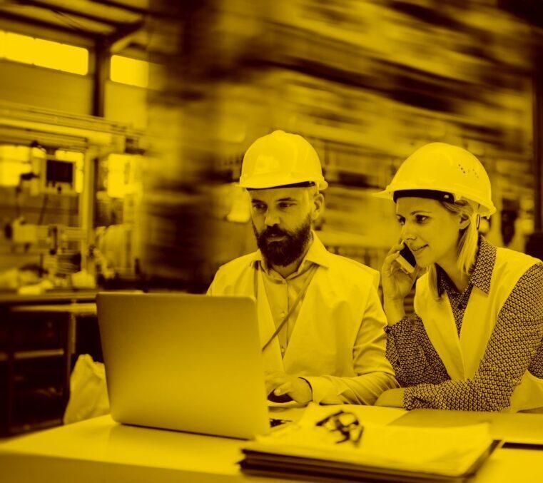 Bauarbeiter und Arbeiterin mit PC und Labelwin im Büro in der maja.cloud