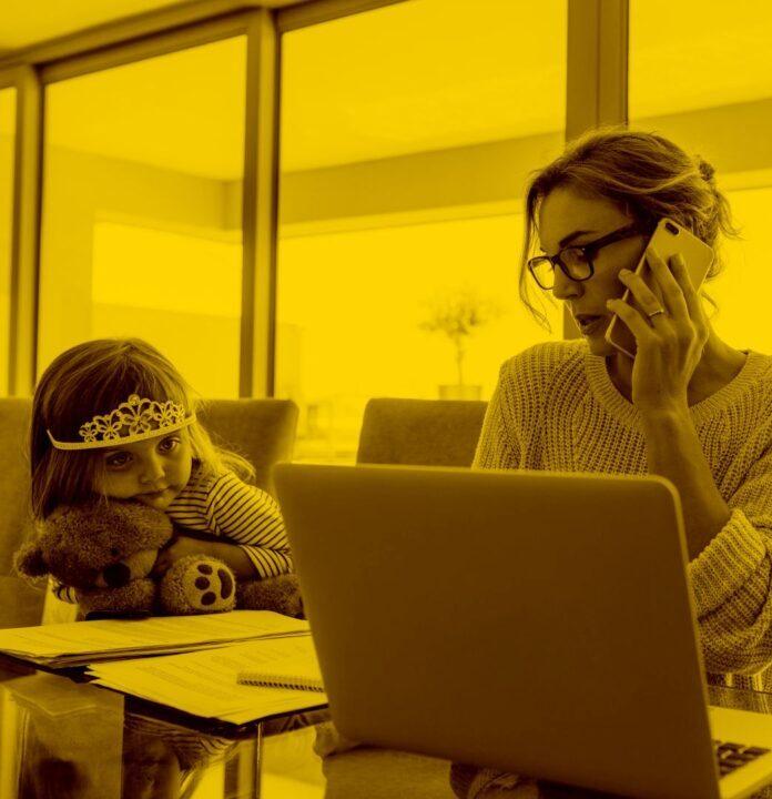 Bauarbeiterin telefoniert mit Arbeitgeber während sie Labelwin auf dem Laptop öffnet