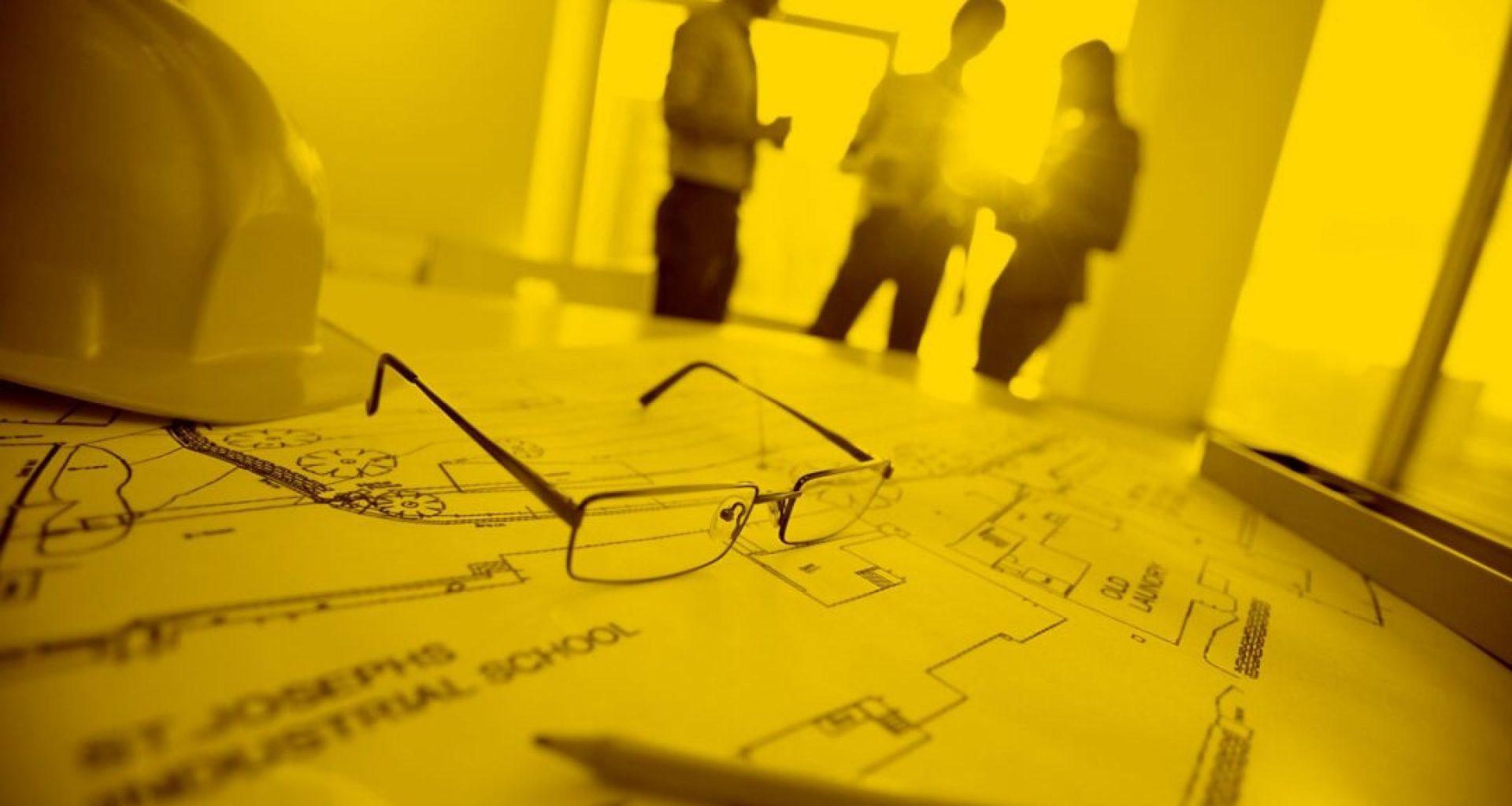 Schreibtisch mit Bauzeichnungen,Bauhelm und eine Brille, im Hintergrund 3 Personen