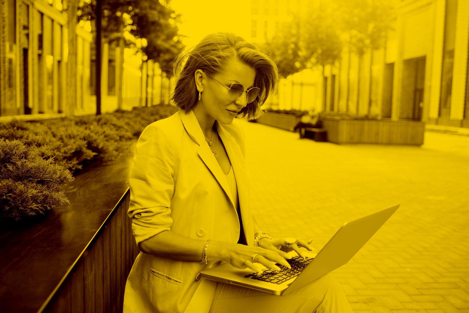 Unternehmerin arbeitet auf einer Sitzbank mobil von der maja.cloud