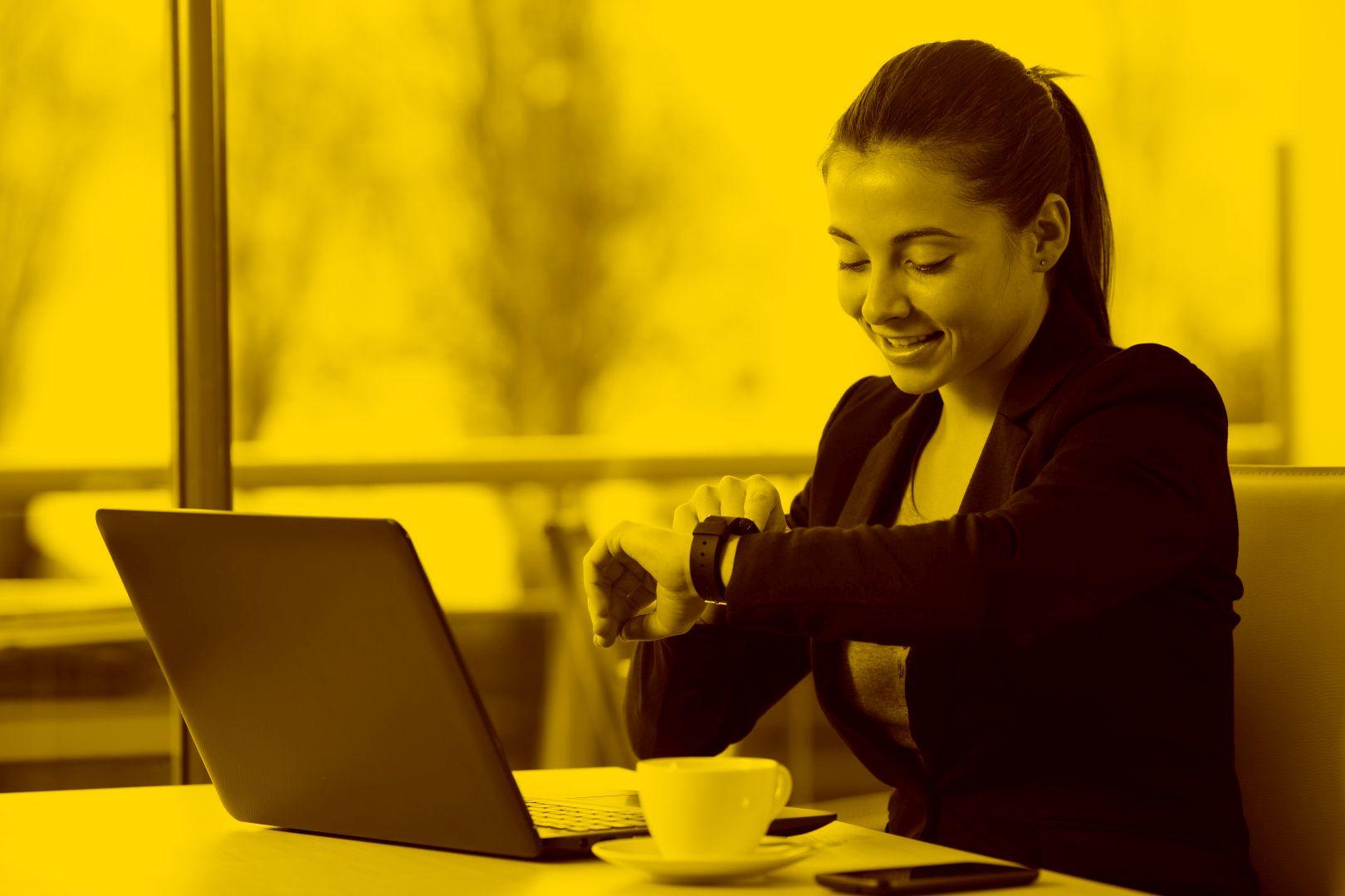 Versicherungsmakrlerin arbeitet mit Salia Maklersoftware in der maja.cloud und guckt auf ihre Uhr
