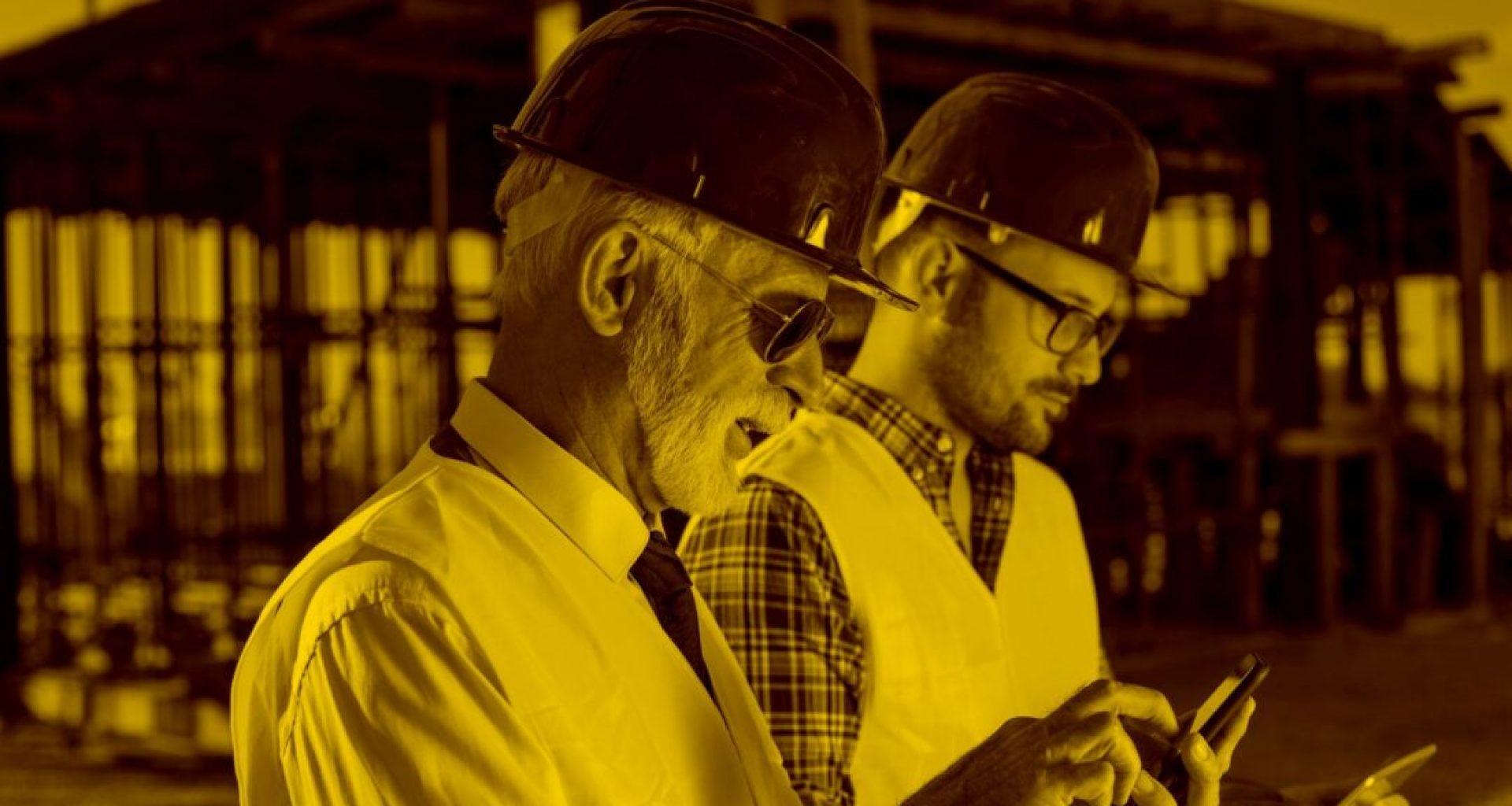 Zwei Bauarbeiter mit Tablet und Smartphone arbeiten mit Offerte L in der maja.cloud