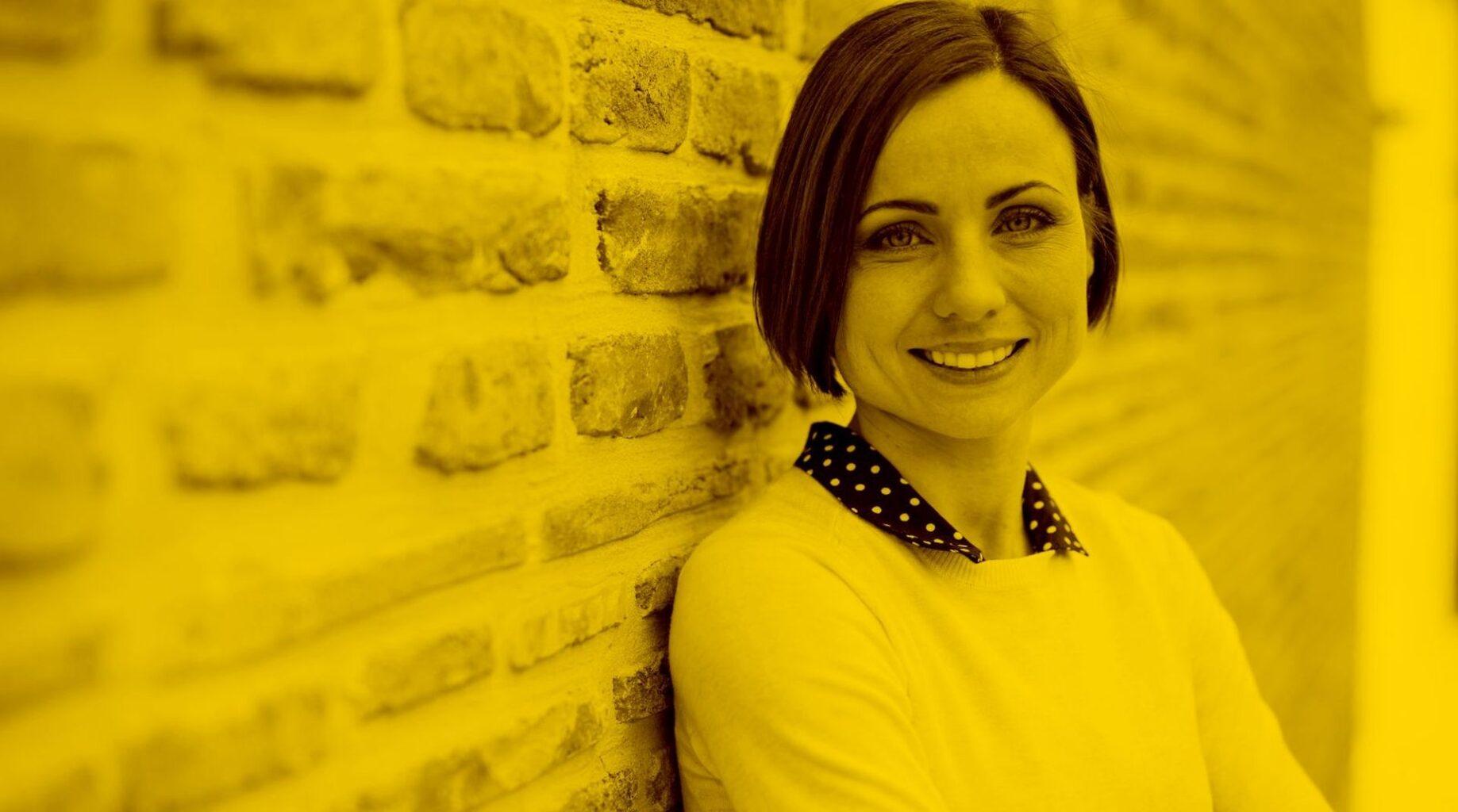 Frau steht vor einer Wand und lächelt