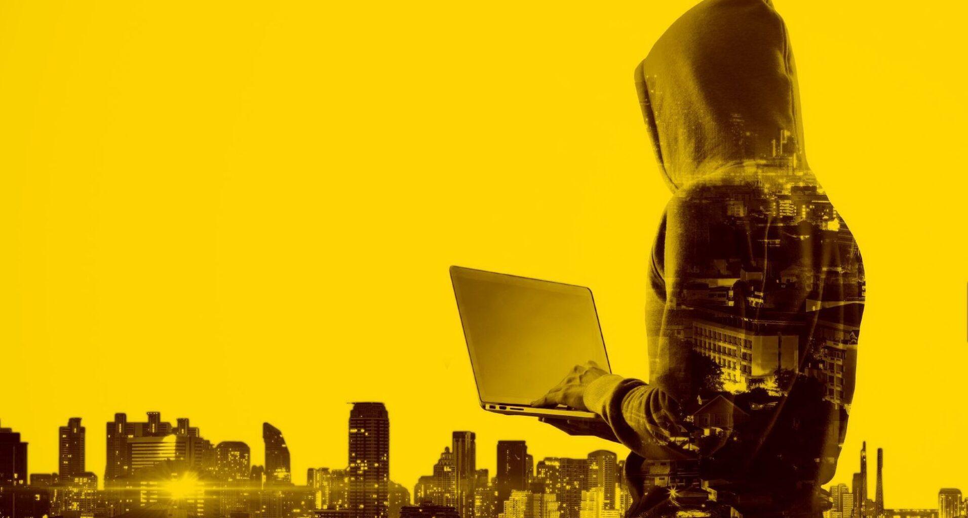 Verdeckter Hacker mit einem Laptop vor Gebäuden