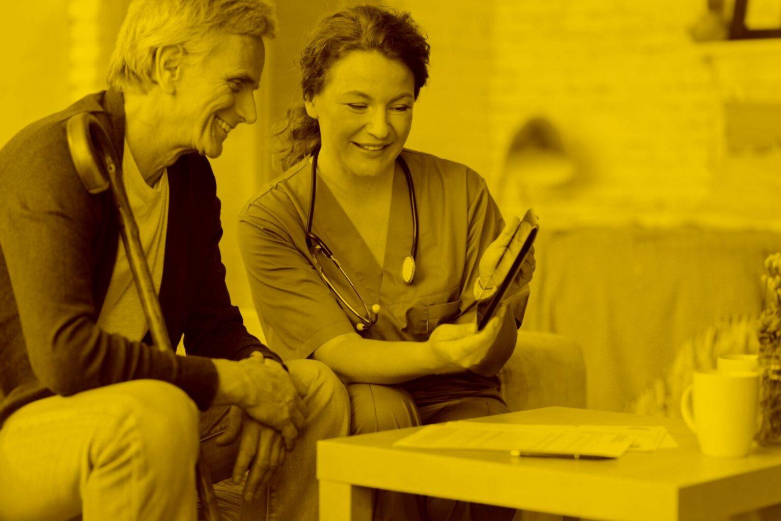 pflegerin-zeigt- senior-tablet-mit- easysoft-in- der- maja.cloud